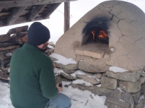 Caleb stoking the pizza oven