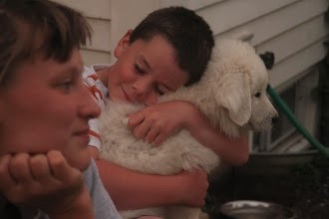 Seamus snuggling a puppy
